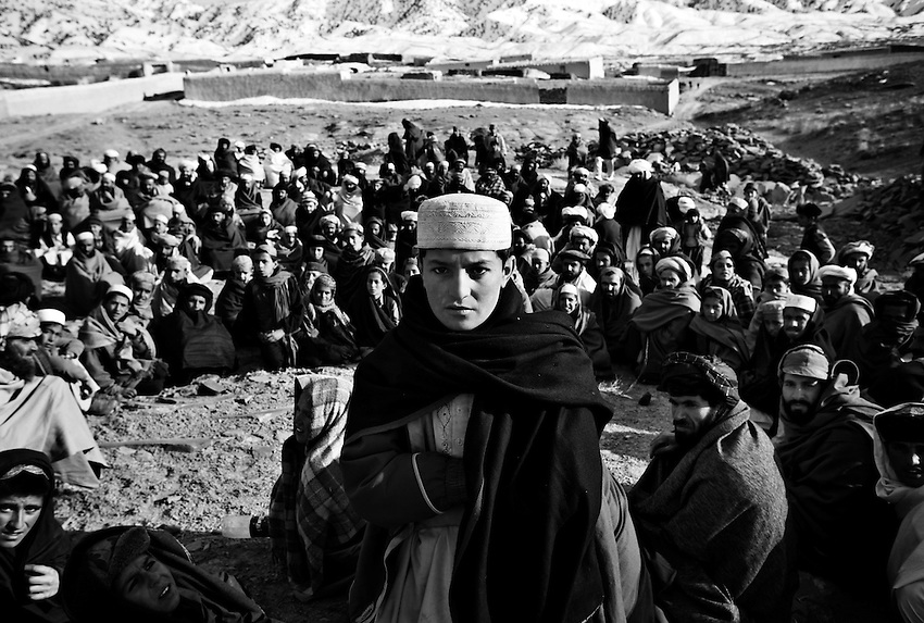 Afghans gather to receive humanitarian aid after an operation conducted by members of Baker Company, 1/506th Infantry, the Afghan National Army and Afghan Military Police in the village of Marzak, Paktika Province, Afghanistan, Thursday, Feb. 26, 2009.