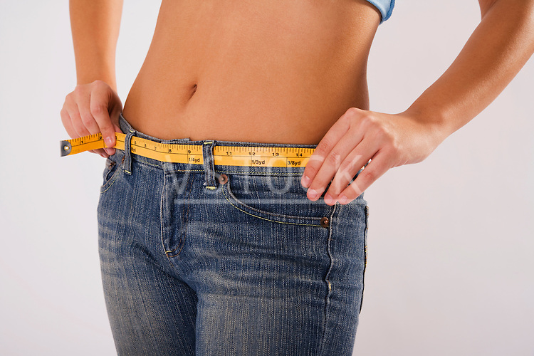 Woman measuring waist using tape measure, mid section
