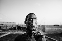 """A man smokes a cigaratte in front of a waste lather processing factory, Hazaribagh tannery area in Dhaka, Bangladesh.  In 2013, the Zurich-based Green Cross Switzerland and the New York-based Blacksmith Institute published a report on the most polluted places in the world. The report """"The Top Ten Toxic Threats, Clean Up, Progress and Ongoing Challenges,"""" puts Hazaribagh at number five. Each day in Hazaribaugh, more than 5,000 gallons of hexavalent chromium is dumped into the Buriganga river."""