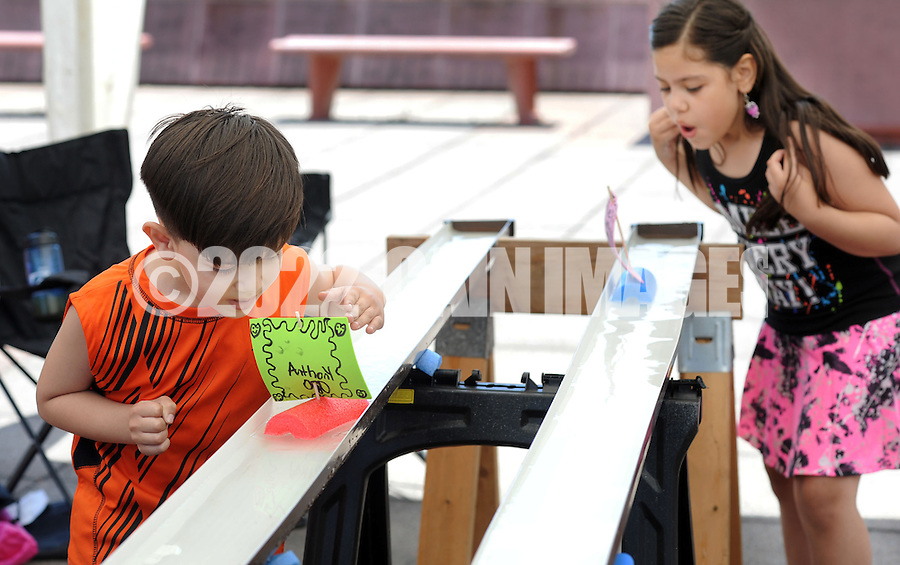 BRISTOL, PA - JUNE 07: Anthony Negron, 6, (L) and Krystal Negron, 8, blow on the sails of their boats during the Boat Regatta June 7, 2014 Bristol, Pennsylvania. Members of Cub Scout and Boy Scout Troop 212 held the event, in which sail boats were made from pool noodles and then raced in a gutter. (Photo by William Thomas Cain/Cain Images)