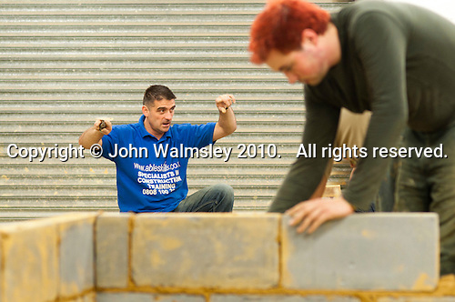 Instructor explaining something to a student on a bricklaying course.  Able Skills in Dartford, Kent, runs courses in construction industry skills like, bricklaying, carpentry and tiling.