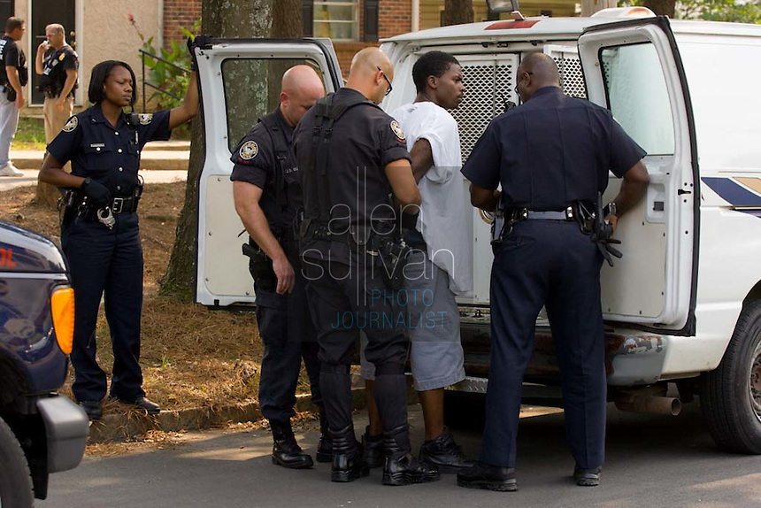 Atlanta Police Department officers detain a man during sweeps in the Vine City Terrace Apartments on Saturday, August 18, 2007. Police said they found drugs, drug money and at least one stolen car during the sweeps, which also included Bowen Homes.