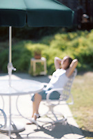 Woman relaxing in sunshine on patio. Defocussed.