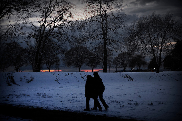 Two people silhouetted, walking together through the snow at dusk. Pink in the sky ahead of them, trees filled with snow.