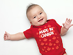Happy smiling four month old baby boy wearing red Made in Canada body suit. Isolated on white background.