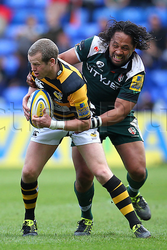 03.04.2011 Wasps Fly Half Dave Walder in possession and being tackled by London Irish Centre Seilala Mapusua Aviva Premiership Rugby from Madejski Stadium. London Irish v London Wasps.