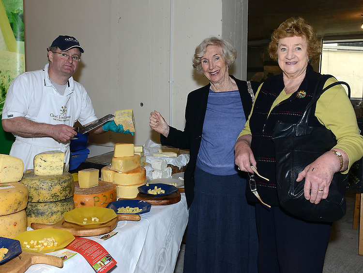 Peter Thomas shows some of his cheeses to Phyllis O'Dwyer and Vera Murphy at the Old Schoolhouse Market. Photo:Colin Bell/pressphotos.ie
