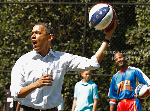 "United States President Barack Obama shoots a basketball while participating in a ""Let's Move"" clinic with members of the NBA, WNBA and the Harlem Globetrotters during the White House Easter Egg Roll on the South Lawn of the White House, Monday, April 25, 2011 in Washington, DC. About 30,000 people are expected to attend the 133-year-old tradition of rolling colored eggs down the White House lawn. .Credit: Chip Somodevilla / Pool via CNP"