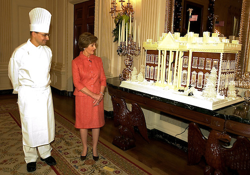 Washington, D.C. - November 30, 2005 -- First lady Laura Bush shows off the White House gingerbread house in the State Dining Room at the White House in Washington, D.C. on November 30, 2005.  At left is Thaddeus DuBois, the White House Executive Pastry Chef, who created the house..Credit: Ron Sachs - Pool