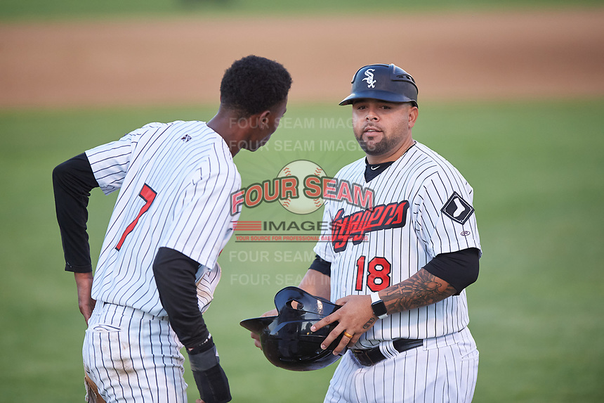 Great Falls Voyagers assistant coach Gerson Montilla (18) talks to Cabera Weaver (7) between innings of a Pioneer League game against the Missoula Osprey at Centene Stadium at Legion Park on August 19, 2019 in Great Falls, Montana. Missoula defeated Great Falls 1-0 in the second game of a doubleheader. (Zachary Lucy/Four Seam Images)