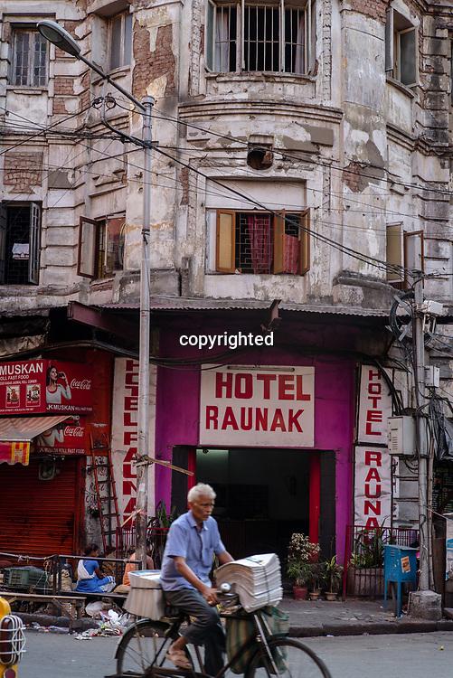 A newspaper vendor rides past the Futnani Chambers, a colonial-era building, in Kolkata, India, on Friday, May 26, 2017. Photographer: Sanjit Das