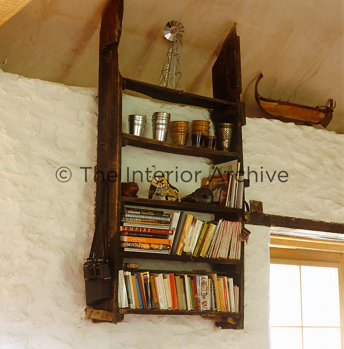 Simple open shelving salvaged from the original barn is incorporated into the living room as a bookshelf
