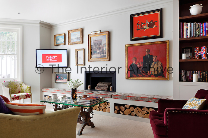 A traditional sitting room with a display of artwork arranged on the wall above a fireplace. A built-in log storage unit has a cushion seating on top.