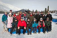 Race Volunteers, tourists and the Rainy Pass lodge owner pose for a group photo at the Rainy Pass checkpoint in the Alaska Range during Iditarod 2009
