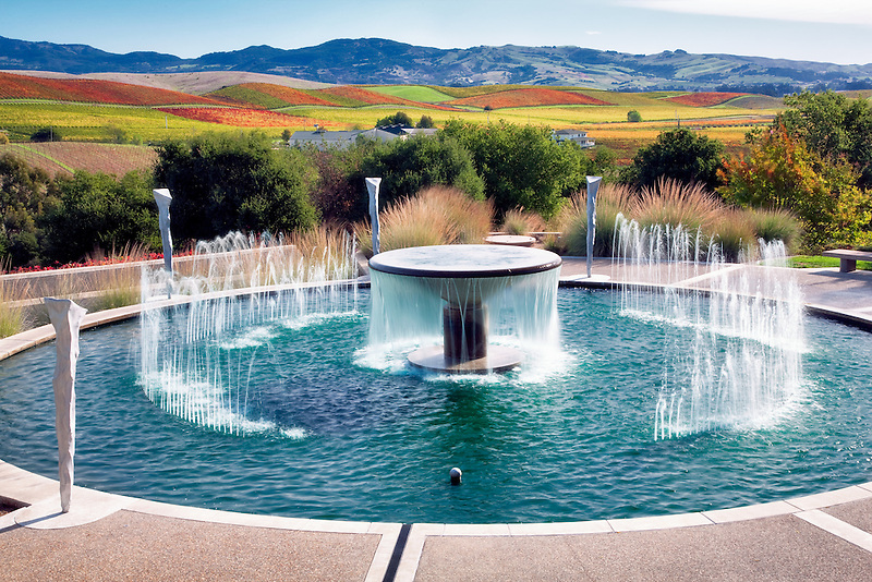 Fountain at Artesia Winery with fall colored vineyards. Napa Valley, California.