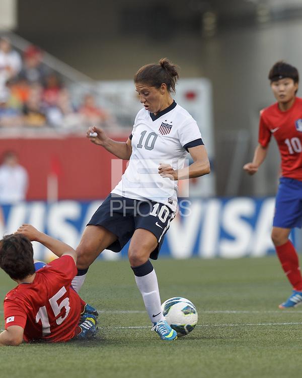 Korea Republic midfielder Kim Narae (15) and USWNT midfielder Carli Lloyd (10) battle for the ball. In an international friendly, the U.S. Women's National Team (USWNT) (white/blue) defeated Korea Republic (South Korea) (red/blue), 4-1, at Gillette Stadium on June 15, 2013.