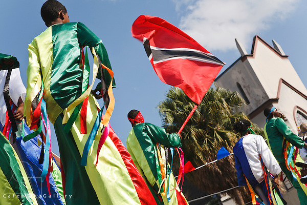 Friday Junior Traditional Mas parade - moko jumbies with national flag