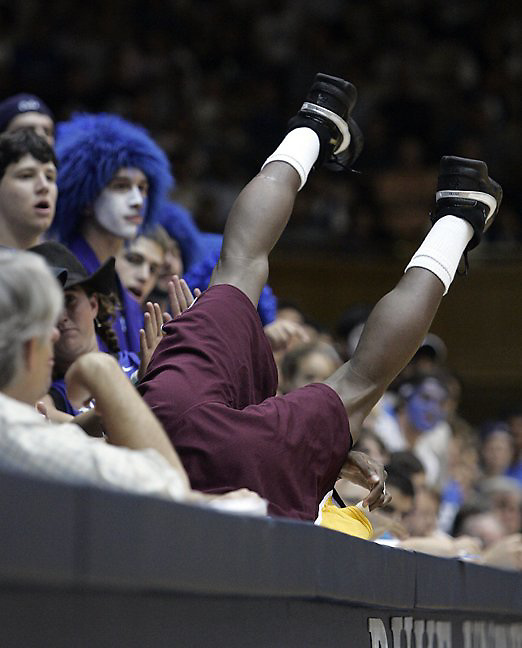 Looking much like the underdog that he was, Shaw University's Cori Gaither goes head-first for a loose ball at the feet of Duke fans and the media at Cameron Indoor Stadium.