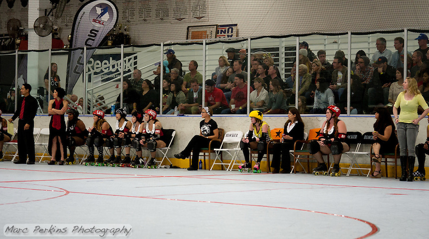 A view of the penalty box setup at the Orange County Roller Girls' home venue of The Rinks.  The two chairs with the black stars on orange backgrounds are for jammers, and sitting in between those two chairs is D'Cup Reffith Ov'r, penalty box manager.  To the left and right of the jammer chairs are blocker chairs, with the blocker timers sitting in the chairs with arms next to those.  A jammer from the Crash Test Bunnies and a blocker from the Psycho Ex Girlfriends are currently sitting in the box.  The team benches are also on this side of the track, and the Psycho Ex Girlfriends' players and coaches can be seen.  The VIP seats OCRG sells are the bleacher seats behind the penalty box and team benches.