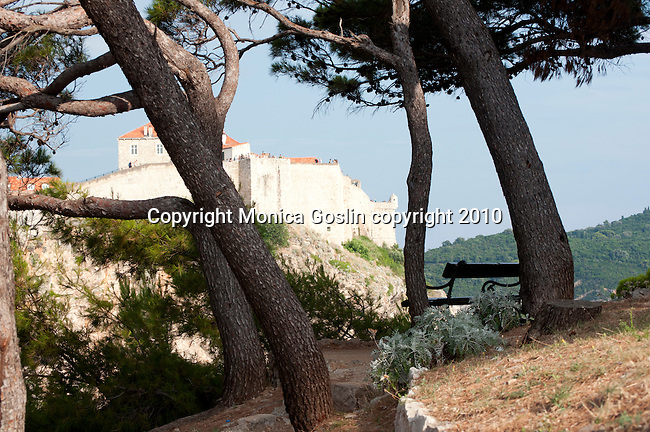 A view of the city wall of Dubrovnik, Croatia through some trees.