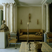A Louis XVI sofa is placed in the centre of the living room flanked by classical columns and surrounded by an eclectic collection of artefacts