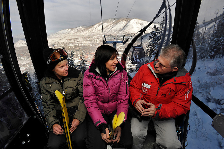 Ski instructor Joe Nevins, right, talks technique during the gondola ride up Aspen Mountain with students Laura Davidson, 57, of Bear Valley, CA, and Shireen Day, 47, of Boulder, CO, center. Michael Brands for The New York Times.