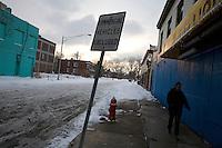 Detroit: paesaggio urbano d'inverno. Una donna cammina in una strada sporca di neve e deserta in mezzo a vecchi edifici.