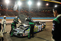 Apr 17, 2009; Avondale, AZ, USA; NASCAR Nationwide Series driver Carl Edwards sits on pit road as crew members look under the hood during the Bashas Supermarkets 200 at Phoenix International Raceway. Mandatory Credit: Mark J. Rebilas-