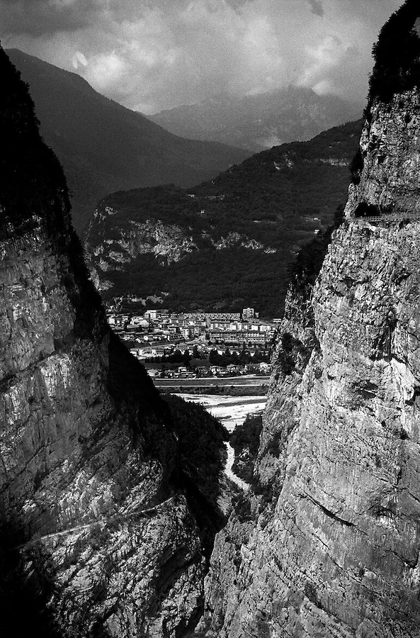 The new town of Longarone as seen through the narrow gorge from top of the dam. On October 9th 1963 a giant landslide collapses into the artificial lake created by the Vajont Dam in northern Italy, provoking a 250 meters high wave that completely destroys the settlements near the lake and the town of Longarone far down in the valley below the dam. 1910 people lost their lives in a tragedy that easily could have been avoided if it was not for the economical and political interests of powerful men dreaming of the tallest dam in the world. A tragedy that is still alive today in Erto, Casso and Longarone, where the survivers of that disastrous day almost 50 years ago are still fighting for their justice.