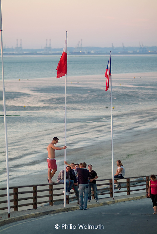Local teenagers at dusk in the Normandy resort of Villierville, close to the port of Le Havre.