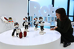"""A woman looks at a demonstration of communication robots called """"Robi"""" during a press preview for """"Robi cafe"""" where visitors can interact with the robots while enjoying meals and drinks in Tokyo, Thursday, January 15, 2015. The robot can be built by assembling parts sent along with a weekly magazine by Deagostini. The cafe will open from January 16 until February 8. (Photo by Yuriko Nakao/AFLO)"""