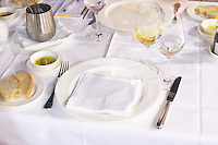 Dinner table set with white table cloth and napkin, knife and fork, wine glasses at the rooftop restaurant Biosphere. Historic town of Mostar. Federation Bosne i Hercegovine. Bosnia Herzegovina, Europe.