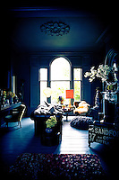 A traditional room decorated in shades of blue with a painted floor. A leather Chesterfield is palced in front of a fireplace and the room has a floor to ceiling arched window.