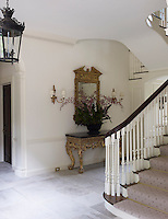 The classical entrance hall is furnished with a giltwood console table and matching gilt-framed mirror