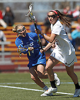Boston College midfielder Caroline Margolis (21) on the attack as Duke University midfielder Chelsea Landon (7) defends.Boston College (white) defeated Duke University (blue), 10-9, on the Newton Campus Lacrosse Field at Boston College, on April 6, 2013.