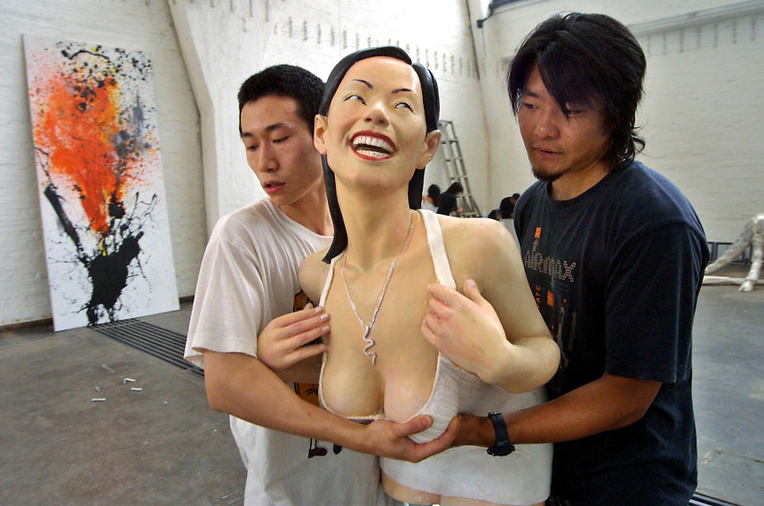 Chinese artists carry a sculpture as they arrange their art works for a weekend exhibition at Gallery 798.