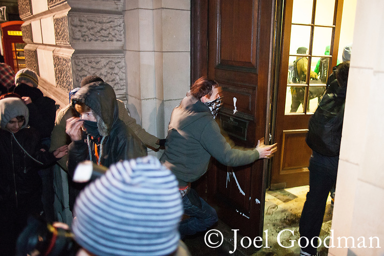 © Joel Goodman - 07973 332324 . 09/12/2010 . London , UK . Several people break through doors of the Treasury and are blocked by police with riot shields .  Students and their supporters clash with police during a demonstration in Parliament Square in London against government cuts to student support , Educational Maintenance Allowance ( EMA ) and rising university tuition fees . Photo credit : Joel Goodman