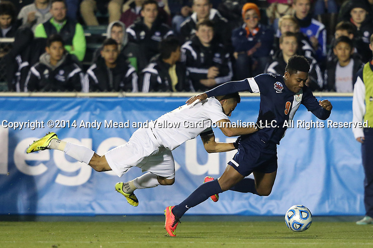 12 December 2014: UMBC's Marquez Fernandez (left) earned a yellow card for this foul on Virginia's Darius Madison (9). The University of Virginia Cavaliers played the University of Maryland Baltimore County Retrievers at WakeMed Stadium in Cary, North Carolina in a 2014 NCAA Division I Men's College Cup semifinal match. Virginia won the game 1-0.