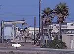 Surfer and oil well at Huntington Beach