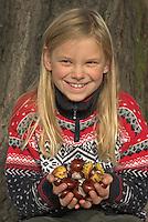 Gewöhnliche Rosskastanie, Roßkastanie, Mädchen, Kind mit gesammelten Kastanien, Ross-Kastanie, Roß-Kastanie, Kastanie, Aesculus hippocastanum, Horse Chestnut, Marronnier d`Inde