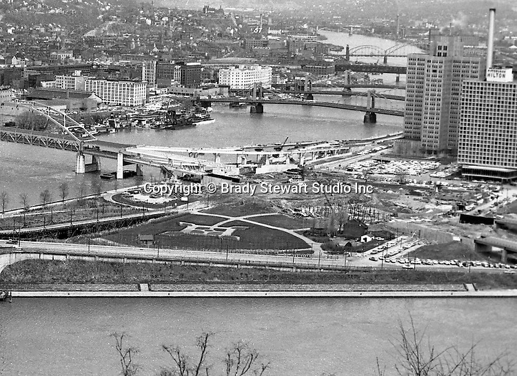 Pittsburgh PA: View of the Point and Fort Duquesne Bridge construction projects - 1962.  View also includes the Allegheny River sister bridges and building on the north side of town.