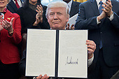 US President Donald J. Trump shows an executive order entitled, 'Comprehensive Plan for Reorganizing the Executive Branch', after signing it beside members of his Cabinet in the Oval Office of the White House in Washington, DC, USA, 13 March 2017.<br /> Credit: Michael Reynolds / Pool via CNP