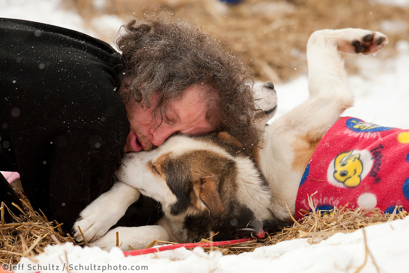 Sebastian Schnuelle gives kisses, pets and hugs to his dogs *Gas* and *Diesel* at Takotna during Iditarod 2009
