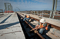 Dallas Area Rapid Transit workers Edgar Godinez (cq, right) and Juan Carrillo (cq, left) work on a new light-rail transit stop for the Green Line in Carrollton, Texas, USA, Thursday, Dec., 3, 2009. The City of Dallas hopes plans to open the new line in 2010...MATT NAGER/ BLOOMBERG NEWS