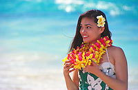 Beautiful polynesian girl with plumeria leis on the beach