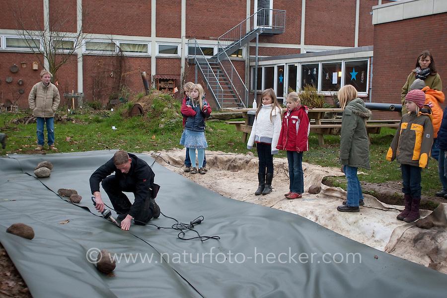 Grundschulklasse, Schulklasse legt einen Schulteich, Schul-Teich, Teich, Gartenteich, Garten-Teich im Schulgarten an, Teichfolie wird verschweisst, verscheißt