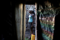 Agare', 14 years old, escaped three years before from her village where she was sold into marriage when she was 8 years old. She stands outside  the shack where she works as a commercial sex worker while waiting for clients in the center of the city of Bahir Dar, a commercial hub in the Northern Amhara region of Ethiopia. The photo was taken on March 3, 2009...While in decline, early child marriage is still widely spread in rural areas of Ethiopia where families sell their daughters into marriage at ages as young as 5 years old...Names of subjects have been fictionalized and specific locations have been omitted to protect the identities of the children portrayed in the story.