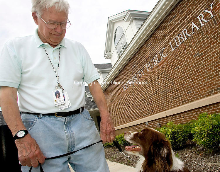 SOUTHBURY, CT -12 JUNE 06- 061206JT02-<br /> Donald Briggs tells his therapy dog Myra to sit beside him in front of the new Southbury Public Library. Although Myra had been allowed in the former library, now the Board of Directors of the library are prohibiting all dogs from entering the library, the reason being that they always had that policy. <br /> Josalee Thrift Republican-American