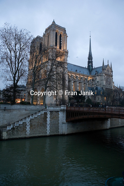 A view of Le Notre Dame from the left bank of the  Seine river on an overcast January day in Paris. The historic catholic church is a classic symbol of Paris.