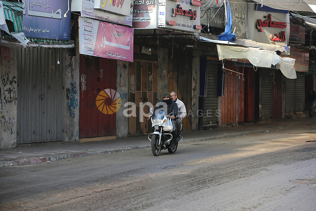 Palestinians walk past closed shops during a general strike against US President Donald Trump's expected peace plan proposal or Deal of the Century,in Khan Younis in the southern Gaza strip on January 29, 2020. Photo by Ashraf Amra